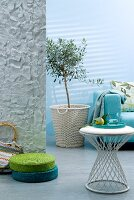 Interior in shades of aqua with sofa, side table & green and turquoise floor cushions