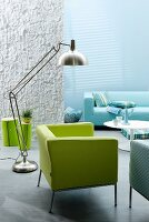 Interior in shades of aquamarine; green armchair, stainless steel designer lamp and blue sofa in background