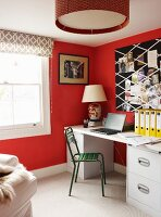 Green metal chair in front of pale desk against red-painted wall and patterned blind on window