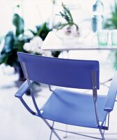 Modern folding chair upholstered in blue in front of a simple table
