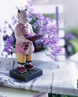 Painted, Asian wooden figure standing on a newspaper