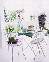 White metal bistro furniture - potted plant with a decorative white metal wicker container next to cups on a table runner