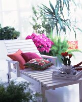 White lacquer outdoor lounger with pillows and potted tulips on a tray