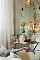Alarm clocks, doll and vase of flowers on vintage side table next to mirror on wall
