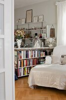 Half-height bookcase as partition next to chaise longue with white cover