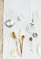 Various kitchen utensils spread out on white tablecloth