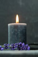 Lit candle amongst dried lavender and flat stones