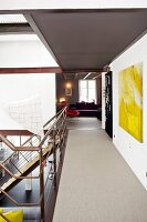 A gallery leading into a living room with a view into an adjoining room