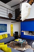 A blue fireplace and yellow accents define the modern style of this open living room with gallery