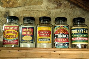 Screw-top glass jars with vintage, English labels on wooden shelf against stone wall