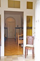 Antique, carved wooden chair in corner of porch and view through open door into hallway with traditional charm