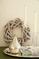White candles in plexiglass candlesticks and silver pear ornament on tray in front of woven wreath leaning on wall