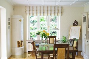 Dining area with antique chairs in front of white tiled corner fireplace and large window in bright dining room