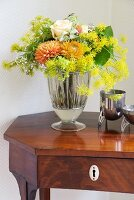 Bouquet in silver vase on antique side table