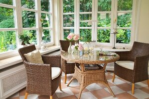 Rattan outdoor furniture on chequered floor of conservatory with view of garden