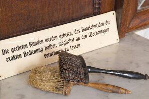 Old barbers' brushes in front of sign in hairdresser's salon
