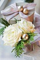 Christmas posy of white roses next to gift box