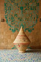 Woven basket in bathroom with a zellige floor and patterned wall tiles