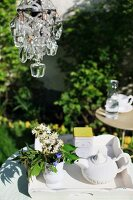 A chandelier above a tray with a porcelain teapot, tea caddy and a jug of flowers in a sunny garden