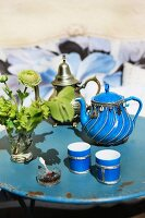 A blue porcelain teapot with silver decoration and matching tea tumblers on an old, round, metal garden table