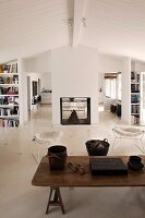 Rustic wooden coffee table and classic chairs in a simple living room with white wood ceiling