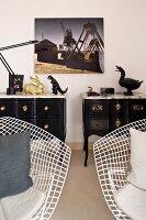 White, bertoia wire chairs in front of a extravagant, black, English style chests of drawers