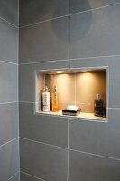 Bathroom with gray wall tiles and bath accessories in an illuminated wall niche