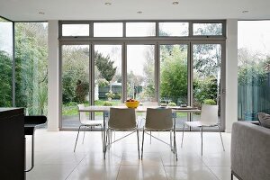 Modern dining table with chairs in front of a bank of windows and view into the garden