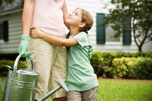 daughter hugging mother carrying watering can