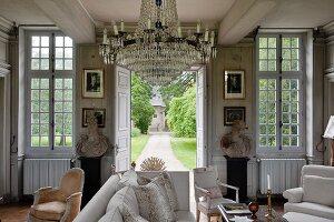 Crystal chandelier in grand living room with open garden doors