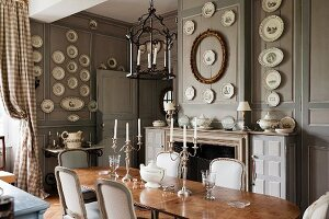 Candlesticks on antique table and pale, upholstered chairs in grand dining room with wall plates on grey-painted, wood-panelled walls