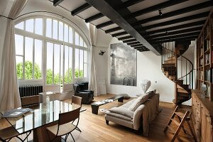 Large arched window in elegant living room with modern dining furniture and minimalist lounge area below mezzanine