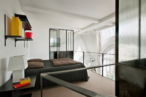 Open-plan sleeping area on gallery - double bed with dark grey bedspread and white art deco table lamp on bedside table