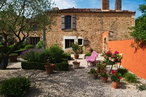 Mediterranean garden of country house with topiary hedges and planters on gravel area with stone wall painted rust red