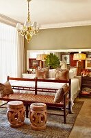 Ethnic side tables at end of double bed in traditional bedroom
