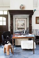 Desk below vintage tiled picture with frame and wooden surround in renovated country house