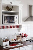 Microwave in a white lacquer floating cabinet on a wall above a kitchen counter with utensils and cook book on a wooden cutting board