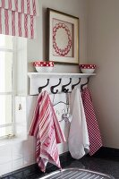 Dish towels hanging on white, lacquer coat rack next to a window in a kitchen corner