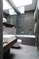 Designer bathroom with grey-tiled walls and floor