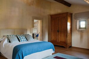 Double bed with blue and white bed linen and rustic wooden wardrobe within historical walls of Proven