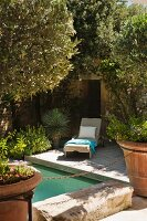 Sun lounger on wooden deck next to pool surrounded by Mediterranean plants