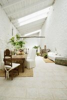 Spacious loggia of white, Mediterranean house with covered chairs and antique chair at rustic table