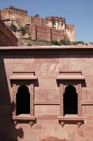 Exterior facade and windows of Raas Haveli Hotel, Jodhpur, India with view of mountain fortress