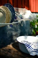 Washing-up bowl on wooden table below drying rack of crockery hung on house facade
