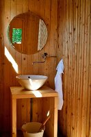 Wood-clad bathroom with simple washstand and round mirror on wall