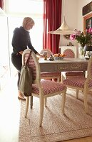 Woman standing at dining table; country-house chairs with red and white hound's-tooth check upholstery