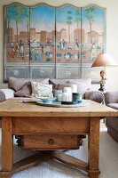 Rustic coffee table and upholstered armchairs in front of multi-panelled picture