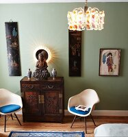 Backlit mirror as halo behind figure of Buddha; antique, Oriental cabinet flanked by classic chairs