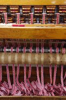 Finished fabric ribbons emerging from loom