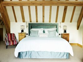 Elegant double bed with sea green valance and upholstered headboard in attic room with wood-beamed ceiling